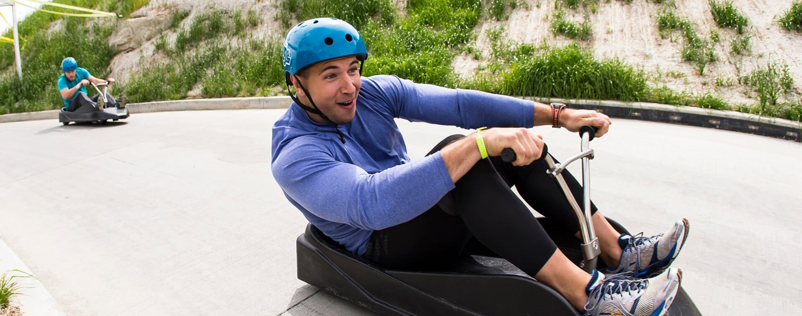 A man smiles as he races round a corner on his downhill kart at Skyline Luge Calgary.