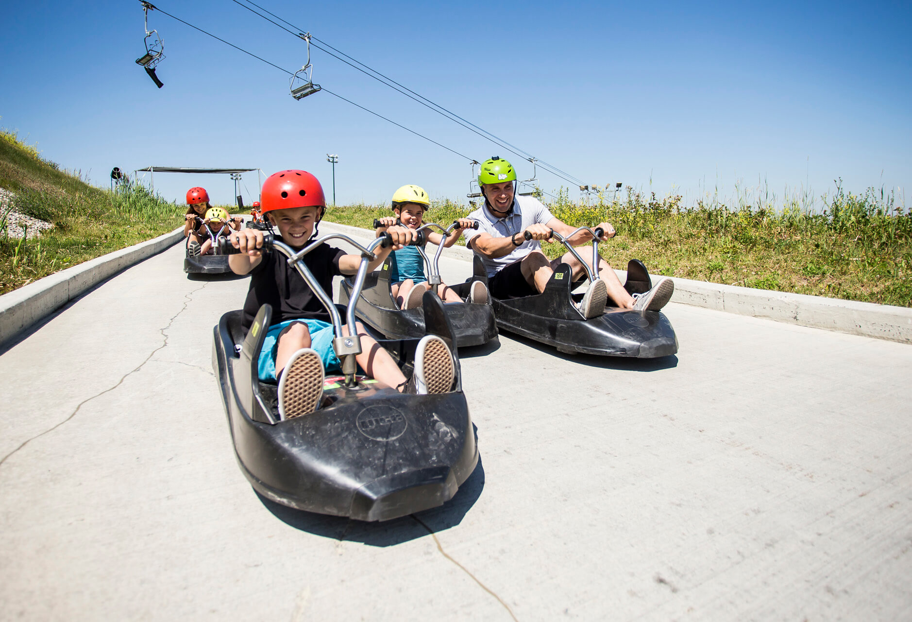 A family rides their downhill karts next to each other as they descend the tracks at Skyline Luge Calgary.