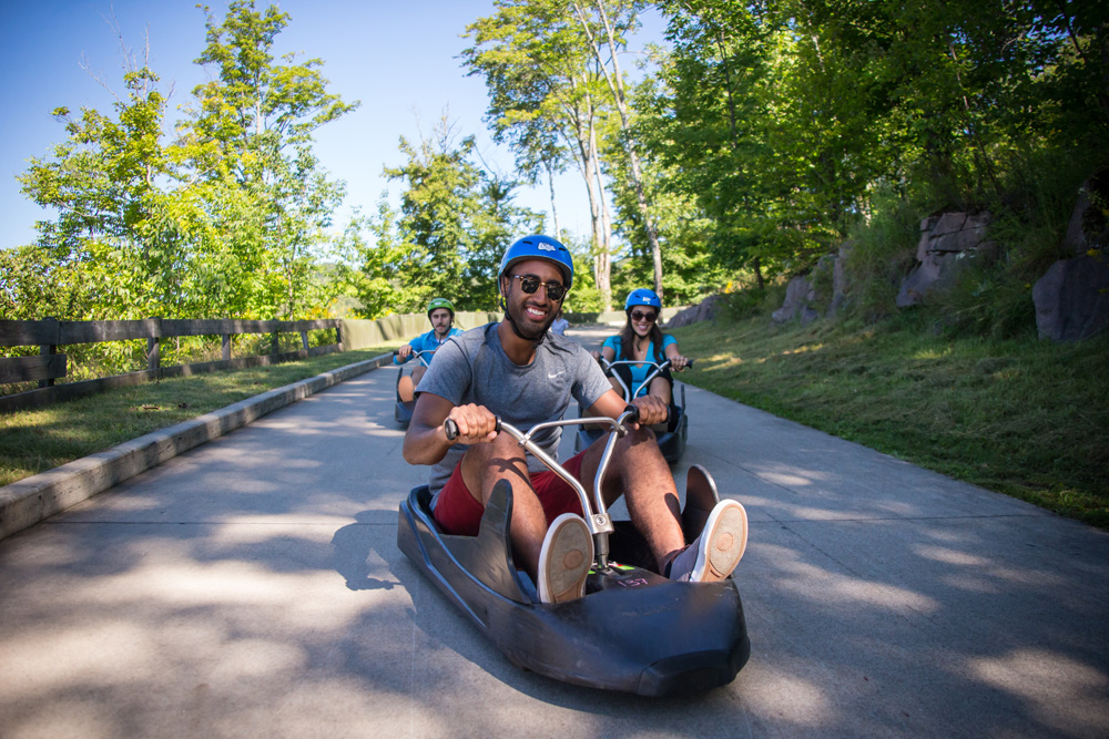 A man smiles as he races his friends on the Luge at Skyline Luge Mont Tremblant.