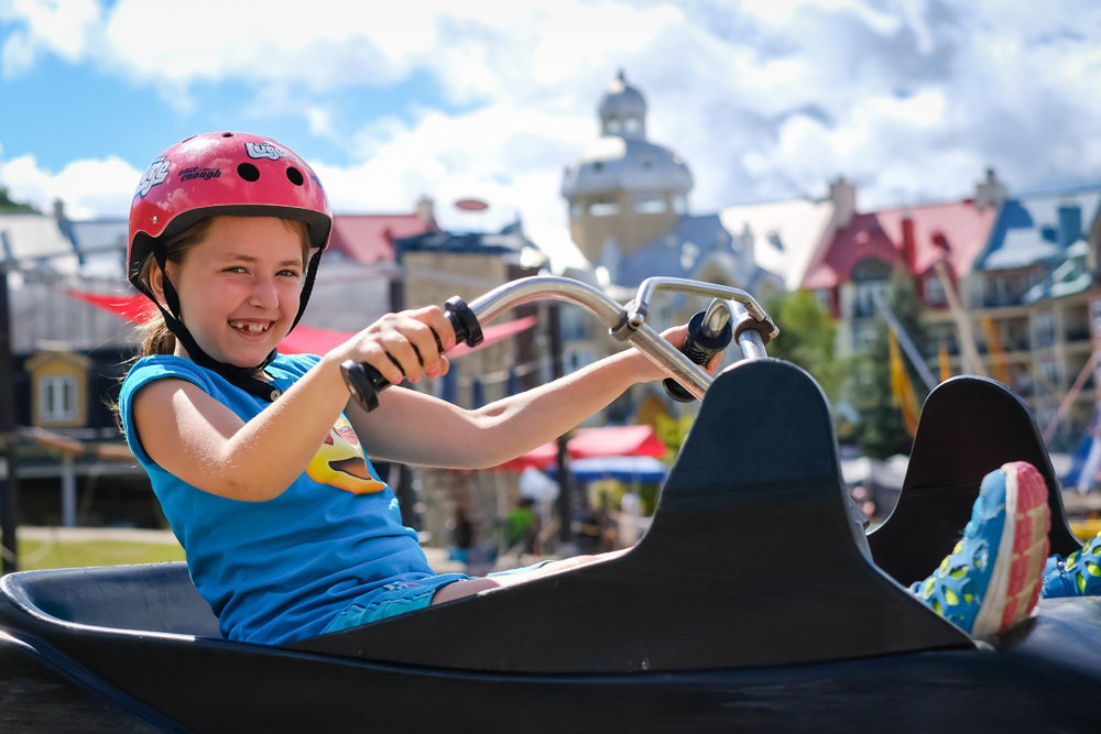 A young girls smiles as she rides her at Skyline Luge Mont Tremblant.
