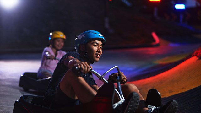 A Man Riding The Night Luge at Skyline Luge Sentosa.