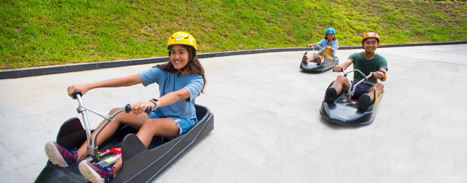 Three Friends Racing Down The Luge Track Together at Skyline Luge Sentosa.