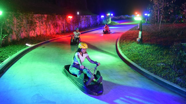 Three Friends Turn A Corner On The Night Luge, Illuminated By Colourful Lights at Skyline Luge Sentosa.