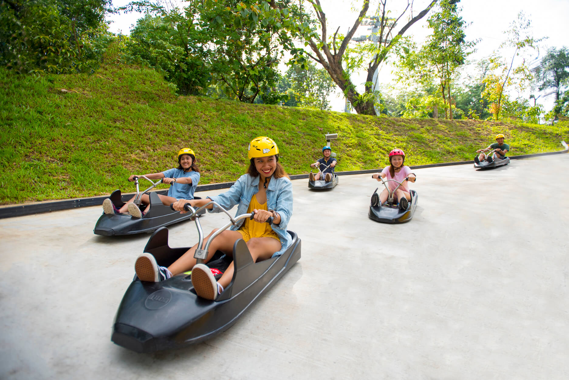 A Group Of Friends Smiling Whilst Riding Their Luge Down The Track at Skyline Luge Sentosa.