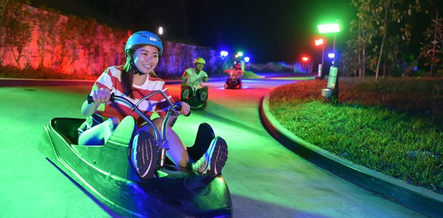 A Woman Riding Her Cart On The Night Luge at Skyline Luge Sentosa.